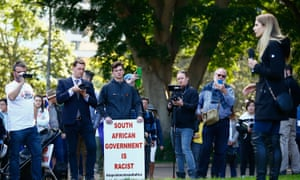 Demonstrators look on as Canadian far-right activist Lauren Southern speaks during a 'Rally for South Africa' demonstration in Sydney, 28 July 2018.