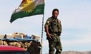 A member of Kurdish peshmerga forces stands aside Kurdish flag on Bashiqa mountain overlooking Isis-held Mosul, 7 March 2015