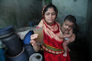 A Bangladeshi woman holds a glass of contaminated water in Dhaka.