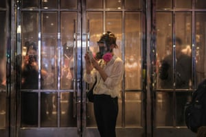 A bystander looks at her mobile phone as police fire teargas to disperse protesters in Causeway Bay.