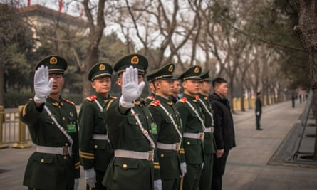 Chinese soldiers gesture towards the photographer as they stand guard in front of the Great Hall of the People.