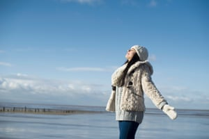 Young woman with arms out, Brean Sands, Somerset, EnglandPosed by model Breathing fresh air at the beach GettyImages-480812475