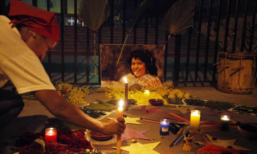A woman places a candle in front of a picture Berta Cáceres outside the Supreme Court in Tegucigalpa, Honduras on 16 September.