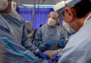 Anaesthesia associates Chris Leck and Alex Balynn and staff nurse Rebecca Lennon prepare a patient for proning. It takes a team of seven people to turn a patient with precise, safe motions onto their stomach so they are lying face down. The prone position allows for better breathing.