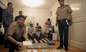 A Peruvian policeman holds a brick of cocaine following a raid