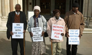 Kenyan campaigners hold placards outside the Royal Courts of Justice