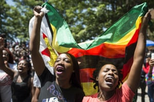 University of Zimbabwe students wave a national flag outside the campus in Harare.