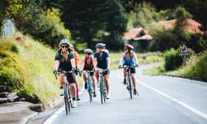 A group of female cyclists go uphill on the border between France and Spain.