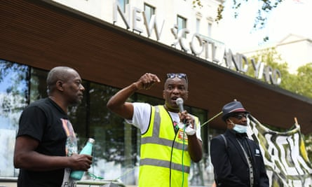 Stafford Scott (centre) speaks outside New Scotland Yard in London, as part of an anti-racism demonstration calling for Metropolitan police commissioner Cressida Dick to resign.