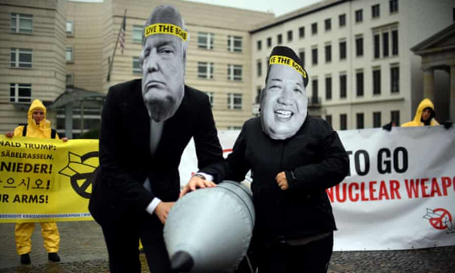 """Activists of the non-governmental organization """"International Campaign to Abolish Nuclear Weapons (ICAN)"""" wear masks of US President Donal Trump and leader of the Democratic People's Republic of Korea Kim Jon-un while posing with a mock missile in front of the embassy of Democratic People's Republic of Korea in Berlin, on September 13, 2017. / AFP PHOTO / dpa / Britta Pedersen / Germany OUTBRITTA PEDERSEN/AFP/Getty Images"""