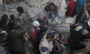 Rescue workers try to pull victims from the debris of a collapsed hospital in Idlib, Syria.