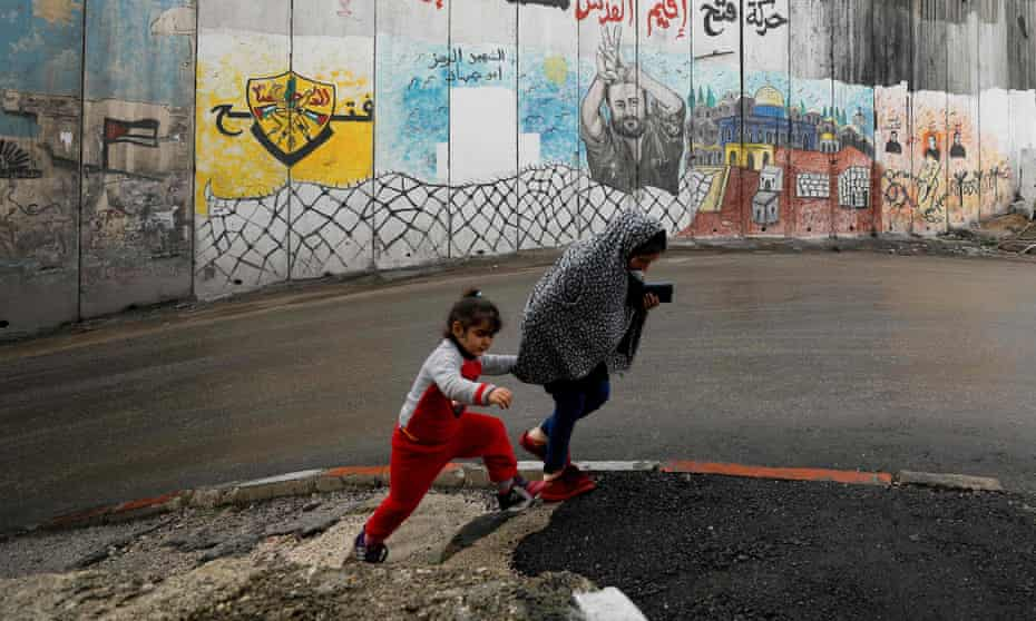 Two children walk in front of a mural painted on the Israeli-built wall dividing Abu Dis from east Jerusalem.