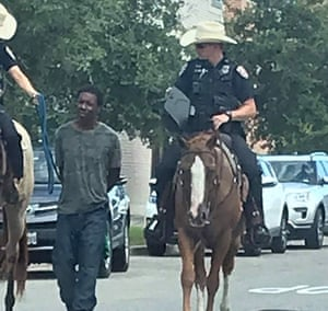 Donald Neely, center, described as homeless and mentally ill, is walked with handcuffs and a rope by two mounted police officers in Galveston, Texas.