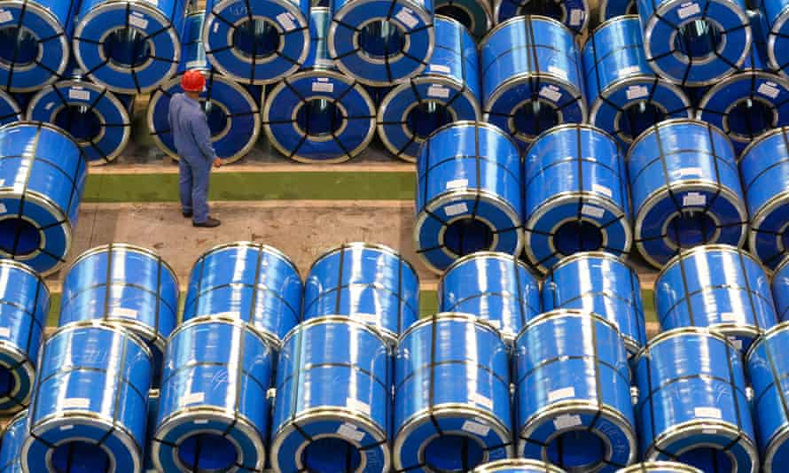 A worker examines rolls of steel at a plant in Taiyuan, China
