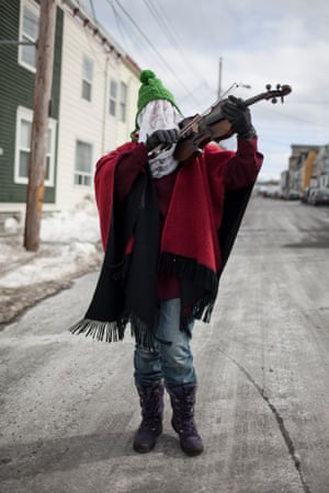 """A masked and hatted fiddle player performs on the streets of St John's, Newfoundland. The Mummer's Song lyrics include some warnings to over-exuberant mummers: """"Ah, be careful the lamp! Now hold on to the stove. Don't you swing Granny hard, 'cause you know that she's old."""""""