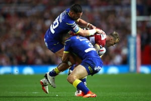Dom Manfredi of Wigan Warriors is tackled by Bryson Goodwin and Bodene Thompson of Warrington Wolves.