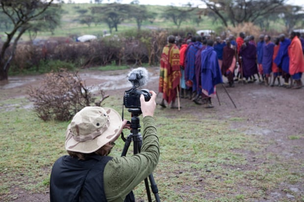 A tourist takes pictures of Maasai villagers.