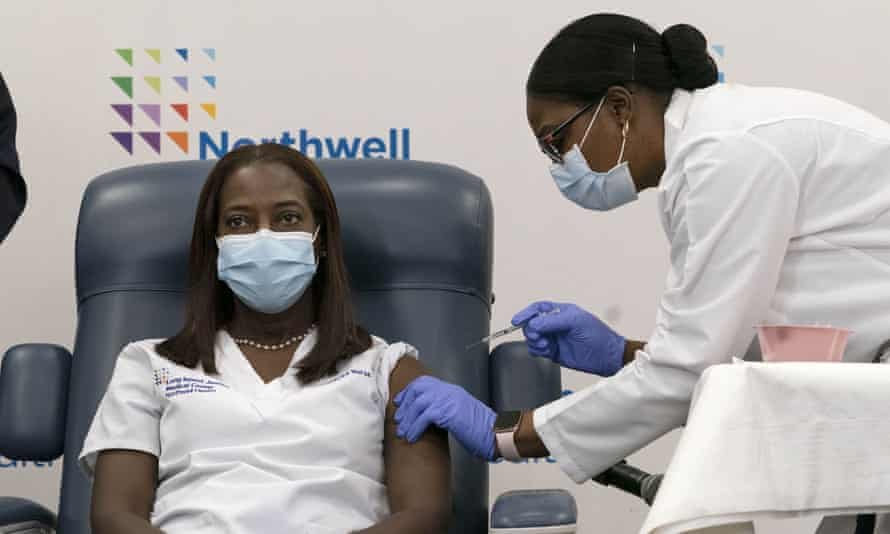 Sandra Lindsay, left, receives the Covid vaccine from Dr Michelle Chester, right, in Queens, New York, inDecember.