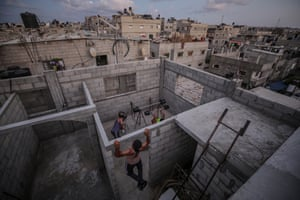 Palestinian bodybuilders work out on the rooftop of a house amid the ongoing coronavirus pandemic in Rafah