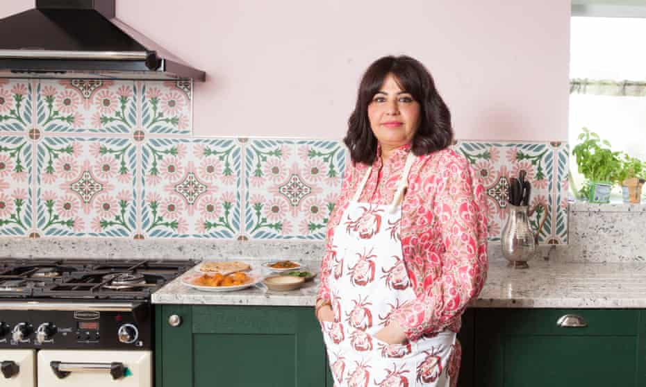 Romy Gill, wearing an apron and leaning against the side with several dishes on it, in her kitchen at her home