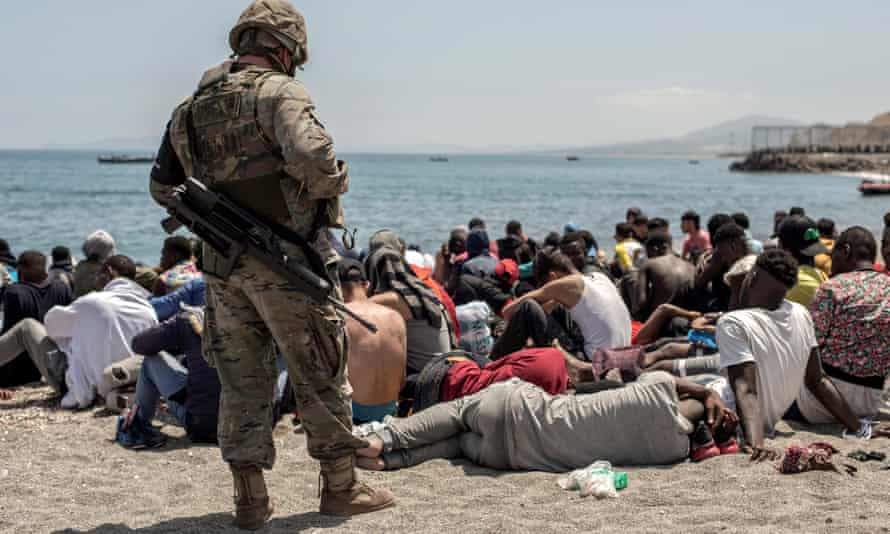 A Spanish soldier looks at people who have swum over the border from Morocco into Ceuta on Tuesday
