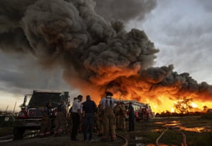 Carolina, Puerto Rico: Emergency services personnel at the scene of a fire at a recycling plant