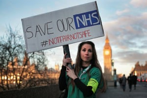 A junior doctor holds up a 'save our NHS' banner outside St Thomas' hospital in London