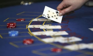 A croupier deals cards on a black jack table