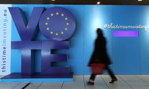 A woman walks past a sign encouraging people to vote in the EU elections at Schuman railway station in Brussels