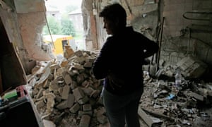 A woman inspects her damaged house on Thursday after shelling in Gorlovka, eastern Ukraine.