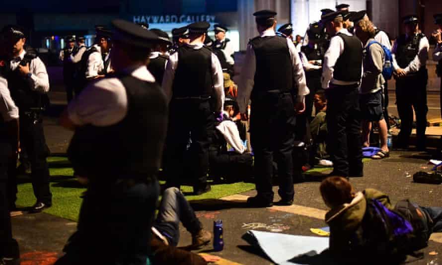 Police remove Extinction Rebellion demonstrators from Waterloo Bridge in London on Sunday night.