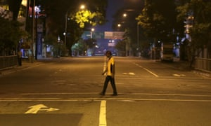 A man walks across a deserted street during a curfew in Colombo
