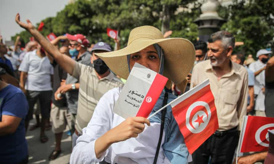 A young woman holds a copy of the 2014 Tunisian constitution at a demonstration in Tunis
