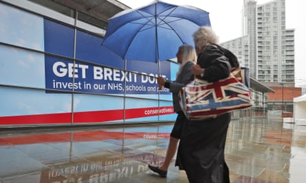Delegates arrive in heavy rain at the conference on Tuesday.