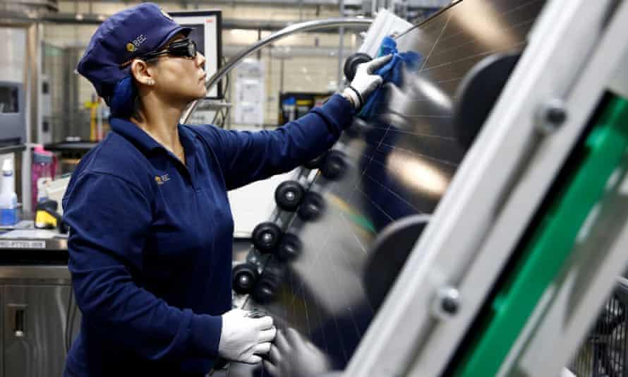 Worker inspects solar panels