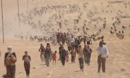 In August 2014, displaced Yazidis flee violence from forces loyal Isis in Sinjar town, heading for the Syrian border