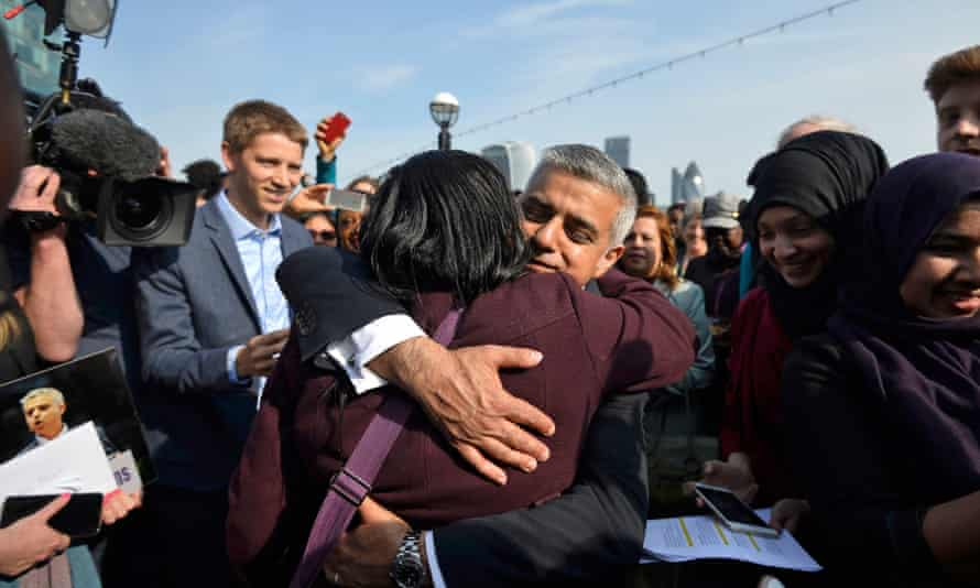 Britain's newly elected mayor Sadiq Khan is embraced by a supporter as he arrives for his first day at work at City Hall in London