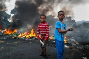 Children stand in front of a blockade in Cape Town's Ocean View township set up in protest over the lack of policing
