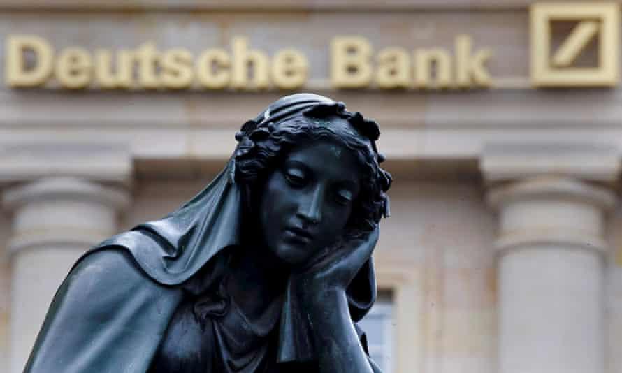 A statue looking sad next to the Deutsche Bank logo