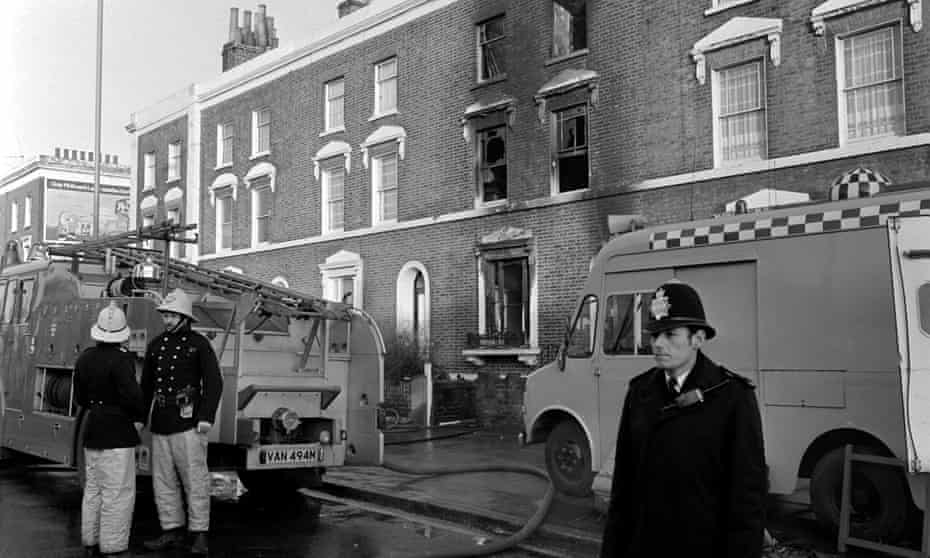 Firefighters and police in front of the fire-ravaged house in New Cross Road, Deptford, south London