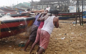 Fishermen pull a boat to higher ground on a beach in Puri