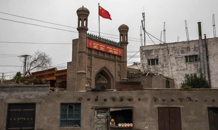 A Chinese flag flies over a local mosque recently closed by authorities as an ethnic Uyghur woman sells bread at her bakery on June 28, 2017 in the old town of Kashgar.
