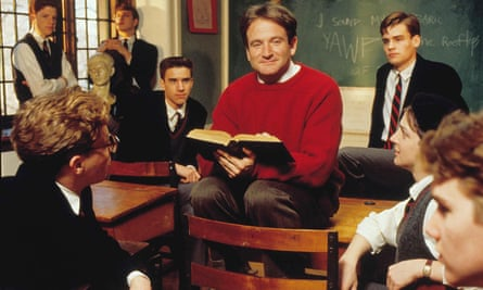 A scene from Dead Poets Society with Robin Williams holding an open book and sitting on a desk in a classroom surrounded by students
