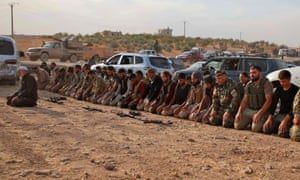 Turkey-backed Syrian fighters kneel to pray as they gather near the village of Qirata on the outskirts of the Manbij.