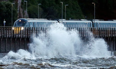 A train passes by strong waves in Dawlish, Devon. Devon and Cornwall police have warned the public to be wary of conditions.