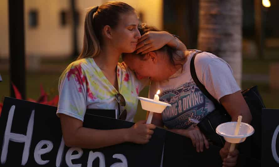 Two women attend a vigil in Boca Raton, Florida, on 16 February for the 17 people killed at a school shooting at Marjory Stoneman Douglas high school.