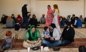 A Sikh family, as well as other visitors to the Sikh Temple of Wisconsin, eats breakfast before prayers.