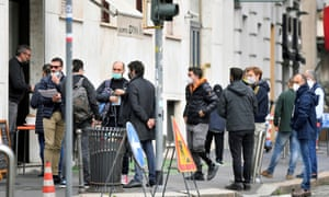 People stand outside a cafe, as the region of Lombardy becomes a 'red zone', closing bars, restaurants and most shops, in Milan, Italy, on Friday.