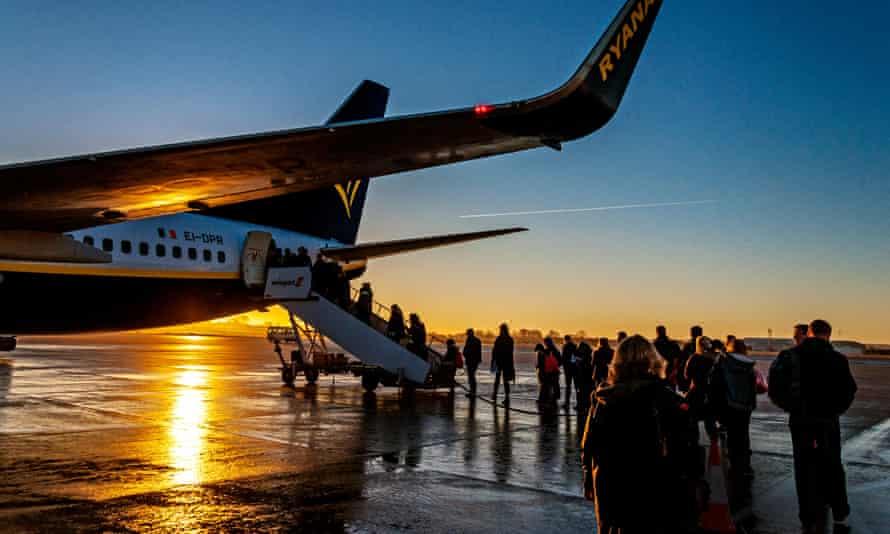 Passengers boarding a Ryanair flight to Dublin at sunrise.