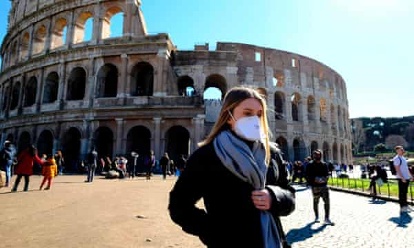 A tourist wearing a protective respiratory mask tours outside the in Rome, 28 February.